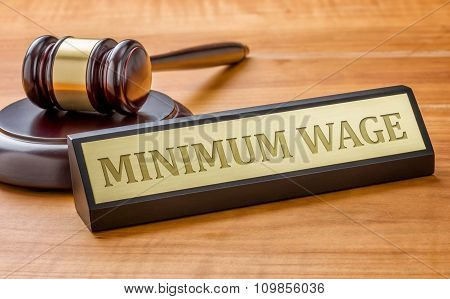 A Gavel And A Name Plate With The Engraving Minimum Wage