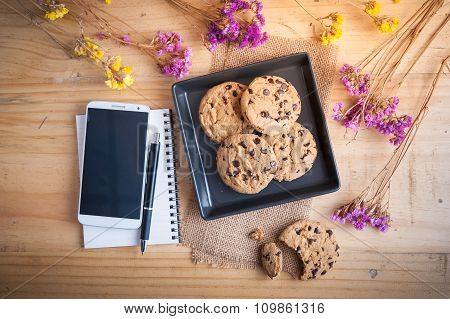 Chocolate chip cookies in black ceramic dish with smartphone notebook and pen at cafe in morning time