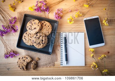 Chocolate chip cookies in black ceramic dish with smartphone notebook with blank area for text or message and pen at cafe in morning time