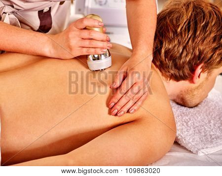 poster of Man receiving electroporation back therapy at beauty salon.
