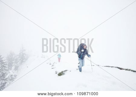 Male and female mountain climbers with huge backpacks and trekking poles having hard hiking trip during winter storm in Austrian Alps poster