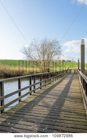 Wooden Bridge With Railing Leading To An Embankment