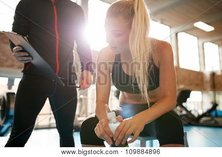 Young Woman With Personal Trainer Looking At Her Fitness Plan