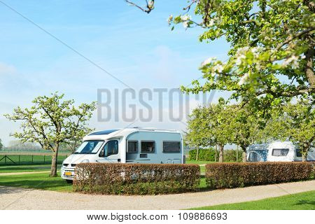Campground with mobile home and caravan in spring