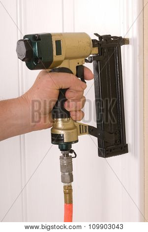 Carpenter using a brad nail gun to complete door framing trim