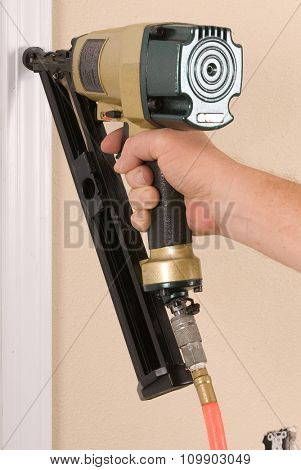Close-up of carpenter using an angle nail gun to complete door framing trim, with the warning label that all power tools have on them shown illustrating safety concept