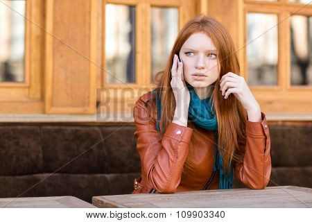 Worried concerned young redhead woman in leather jacket and scarf talking on cellphone in outdoor cafe