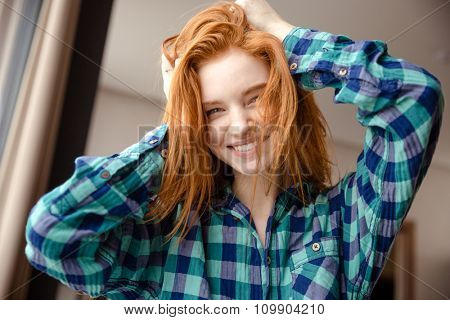 Amusing cheerful funny girl in blue checkered shirt with tousled red hair at home
