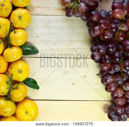 Orange and grapes on the wooden floor