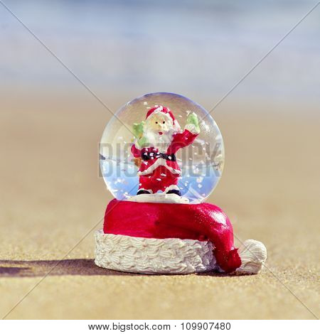closeup of a christmas snow globe with a santa claus in it on the sand of a beach