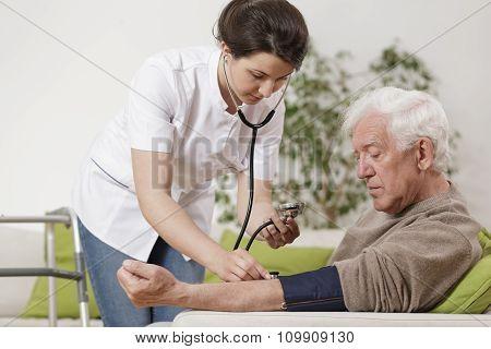 Young Nurse Taking Blood Pressure