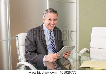 Mature smiling business man using a tablet in his office