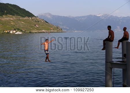 Cully, Switzerland - 8 June 2014: Young Man Walking On Sling In Small Town Of Cully On Lake Geneva,