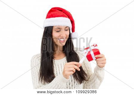 Woman wearing a santa hat holding a red gift with copy space