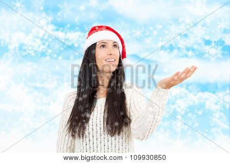 Pretty young woman holding hand up catching snowflakes