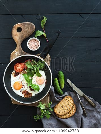 Pan of fried eggs, bacon, tomatoes with bread, mangold and cucumbers on rustic wooden serving board