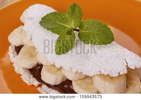 Casabe (bammy beiju bob biju) - flatbread of cassava (tapioca) with banana and chocolate spread on orange plate on wooden table. Selective focus poster