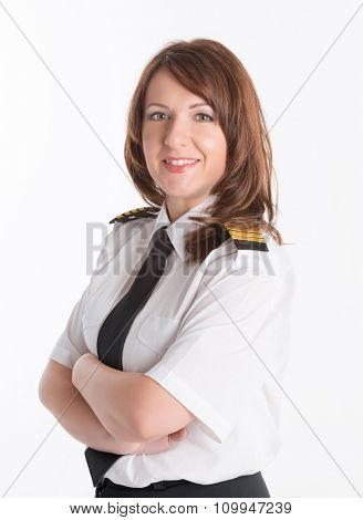 Beautiful woman pilot wearing uniform with epaulets, standing isolated on white background.