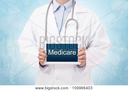 Doctor holding a tablet pc with medicare text on blue background