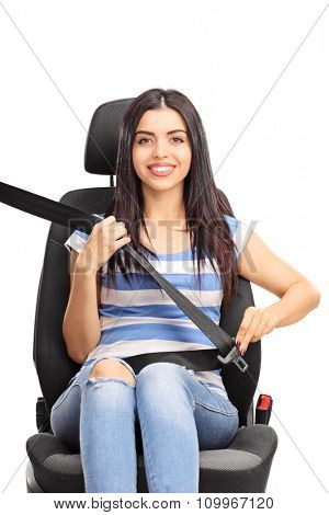 Vertical shot of a young woman sitting on a car seat fastened with a seatbelt and looking at the camera isolated on white background