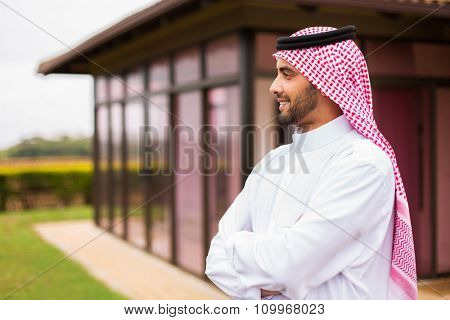 thoughtful arabian man standing in front of his house