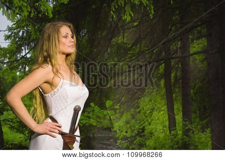 Beautiful Woman In White Dress With Sword In A Wild Forest