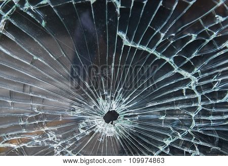 Bullet hole in a shattered piece of glass