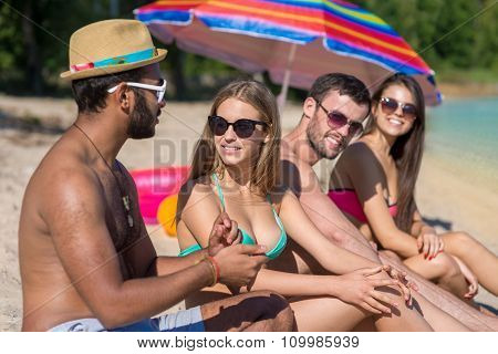 Beautiful young people are sunbathing on the beach.