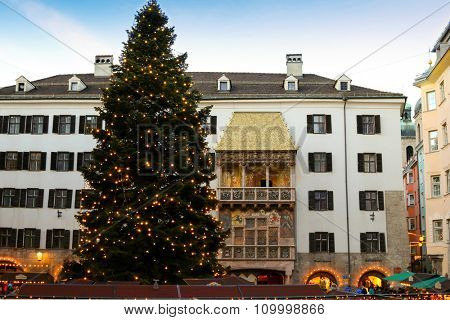 INNSBRUCK, AUSTRIA - DECEMBER 2014 : People walking at Christmas Market with a huge Christmas tree visible in front of the Golden Roof (Goldenes Dachl) in Innsbruck, Austria on December 21, 2014