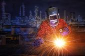 worker with protective mask welding metal and sparks in oil refinary plant. poster
