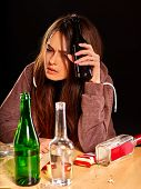 Drunk girl holding bottle of alcohol. Mess on table. Soccial issue alcoholism. poster