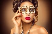 Beauty model woman wearing venetian masquerade carnival mask at party, over holiday background. Christmas and New Year celebration. Sexy girl with holiday makeup and manicure. Red lips and nails  poster