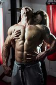 Woman passionately embraces muscular man in the gym. Handsome bodybuilder with a woman poster