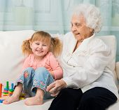 little girl with grandmother sitting on a sofa with toys poster