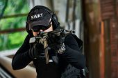 military industry. Portrait of special forces or anti-terrorist police soldier, private contractor armed with assault rifle ready to attack during clean-up operation, mission poster