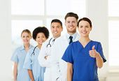 hospital, profession, gesture, people and medicine concept - group of happy doctors showing thumbs up at hospital poster