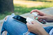 Woman in blue jeans cleans mobile phone antibacterial wipes poster