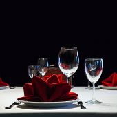 Served table. Romantic restaurant interior with a bright tablecloth, napkins, wine glasses and cutlery. colorful still life and service concept photography poster