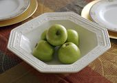 a bowl of apples used as a setting for a holiday dinner table. poster