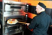 chef baker cook in black uniform putting pizza into the oven with shovel at restaurant kitchen poster