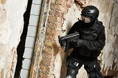 Military industry. Special forces or anti-terrorist police soldier, private military contractor armed with machine gun ready to attack during clean-up operation poster