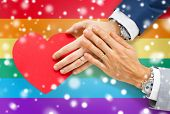 people, homosexuality, same-sex marriage, valentines day and love concept - close up of happy married male gay couple hands with red paper heart shape over rainbow flag background and snow effect poster