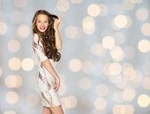 people, style, holidays, hairstyle and fashion concept - happy young woman or teen girl in fancy dress with sequins touching long wavy hair over lights background poster