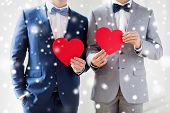 people, homosexuality, same-sex marriage, valentines day and love concept - close up of happy married male gay couple holding red paper heart shapes on wedding over snow effect poster