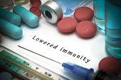 Lowered immunity - diagnosis written on a white piece of paper. Syringe and vaccine with drugs. poster