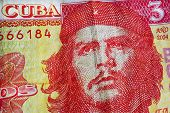 Cuban national hero Ernesto Che Guevara on yellow red banknotes of Cuba bank. Texture of old note of the official cuban currency. poster