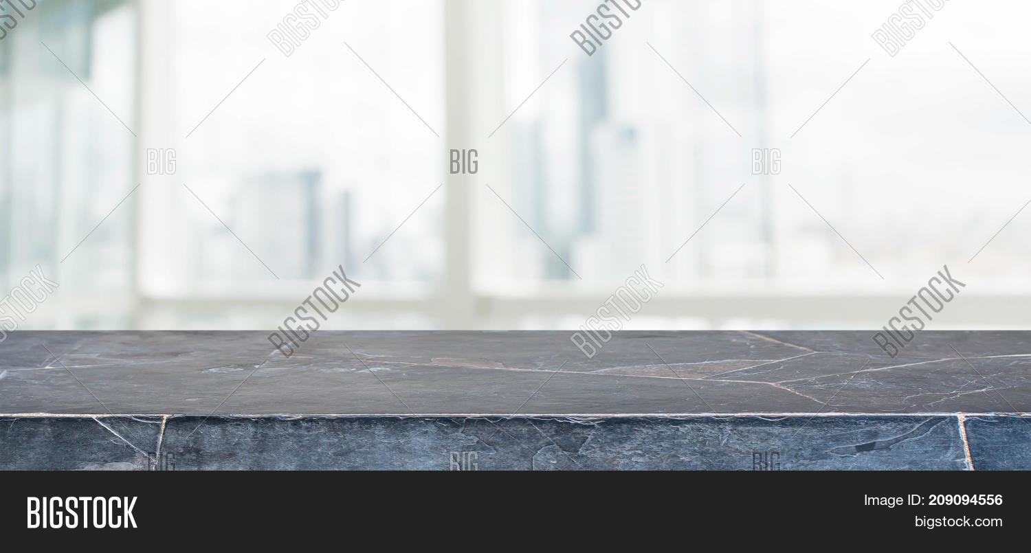 Black Marble Stone Table Top And Blur Glass Window Wall Building With City  View Background
