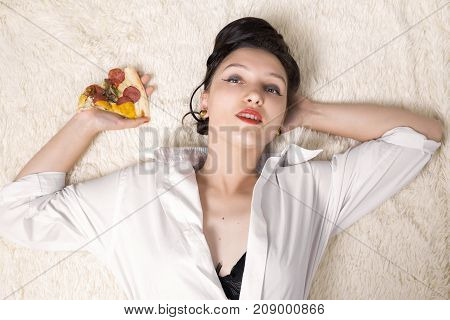 beautiful overeat businesswoman lying with pizza pieces