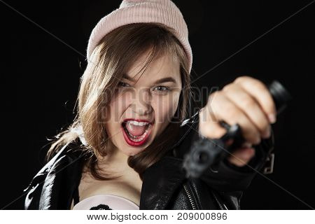 serious girl with gun on black background aiming at camera, screaming