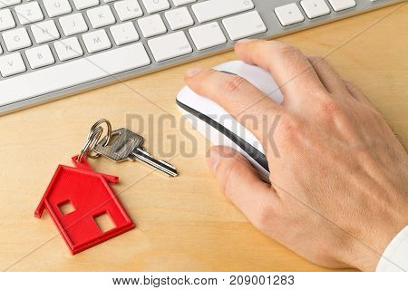 House door key with red house key chain pendant and man using computer on wooden desk - online house rental or purchasing concept